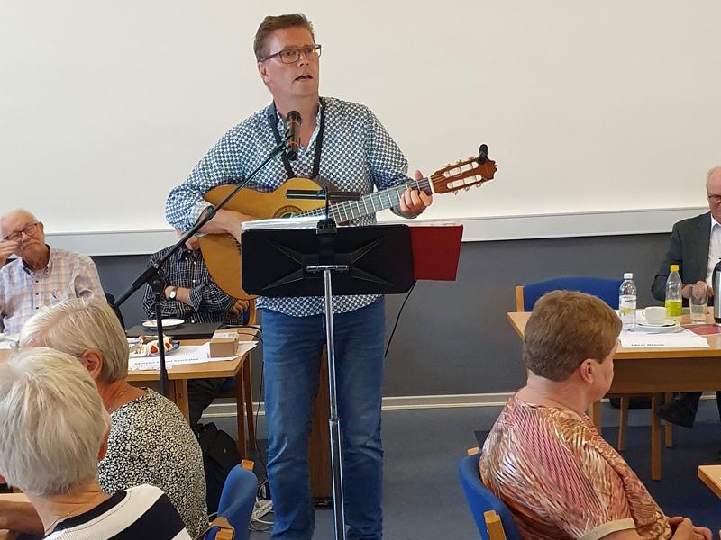De fremmødte medlemmer af Ældre Sagen Bornholm nød de mange dejlige sange, som den bornholmske guitarist og sanger Lars Christiansen fremførte efter årsmødets afslutning. (Foto: Jens Aagesen).